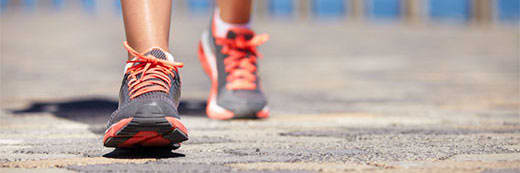 Close up image of person walking down the road in running shoes