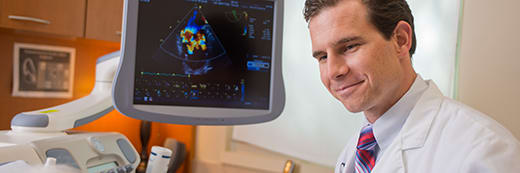 male physician in front of echocardiogram monitor