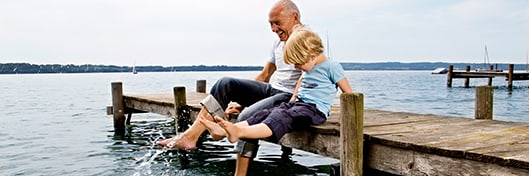 grandfather with grandchild sitting on a waterfront dock splashing feet in the water