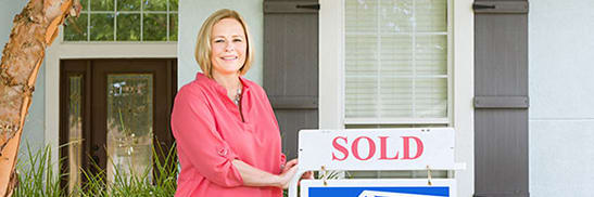 woman standing next to sold realty sign