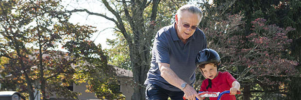 grandfather helping grandson learn to ride a bike