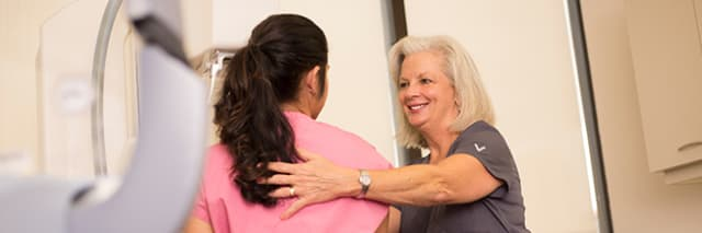 medical worker assisting woman getting a mammogram