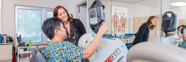 patient on machine with her therapist