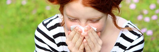 woman blowing her nose in tissue