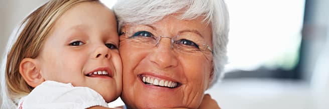 grandmother smiling cheek-to-cheek with granddaughter