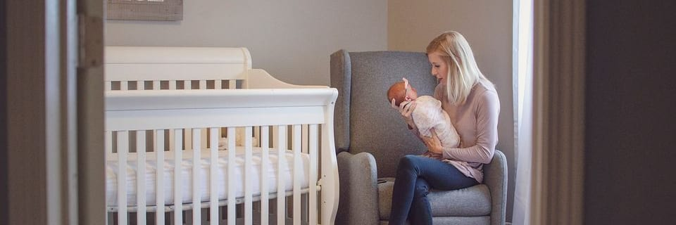 a new mom holding her baby while sitting in a chair in her baby's nursery.