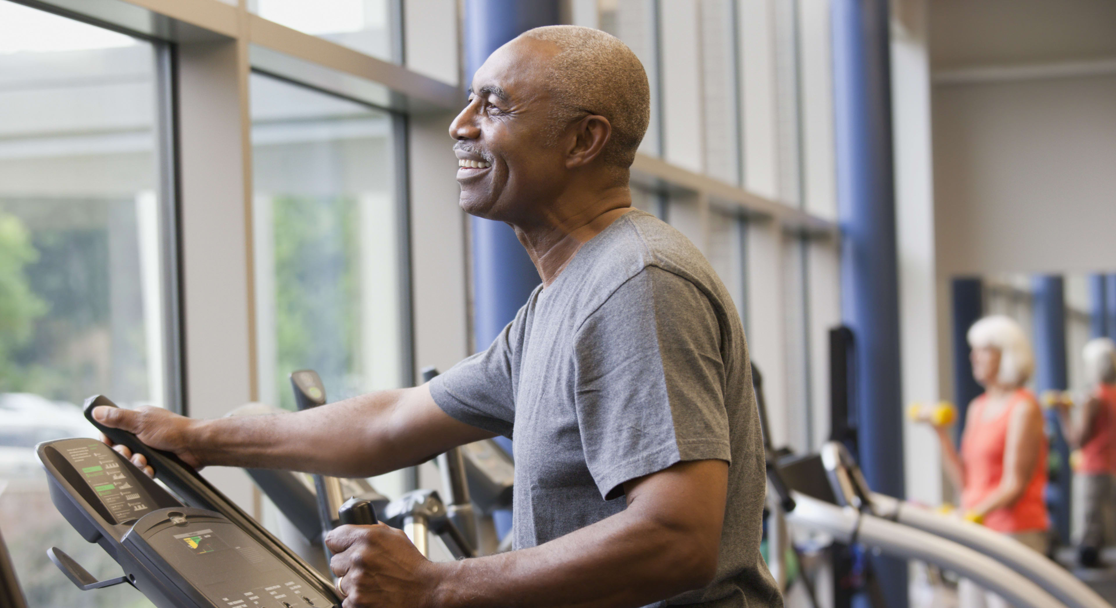 Man exercising on a treadmill at a gym that brightly lit with large windows
