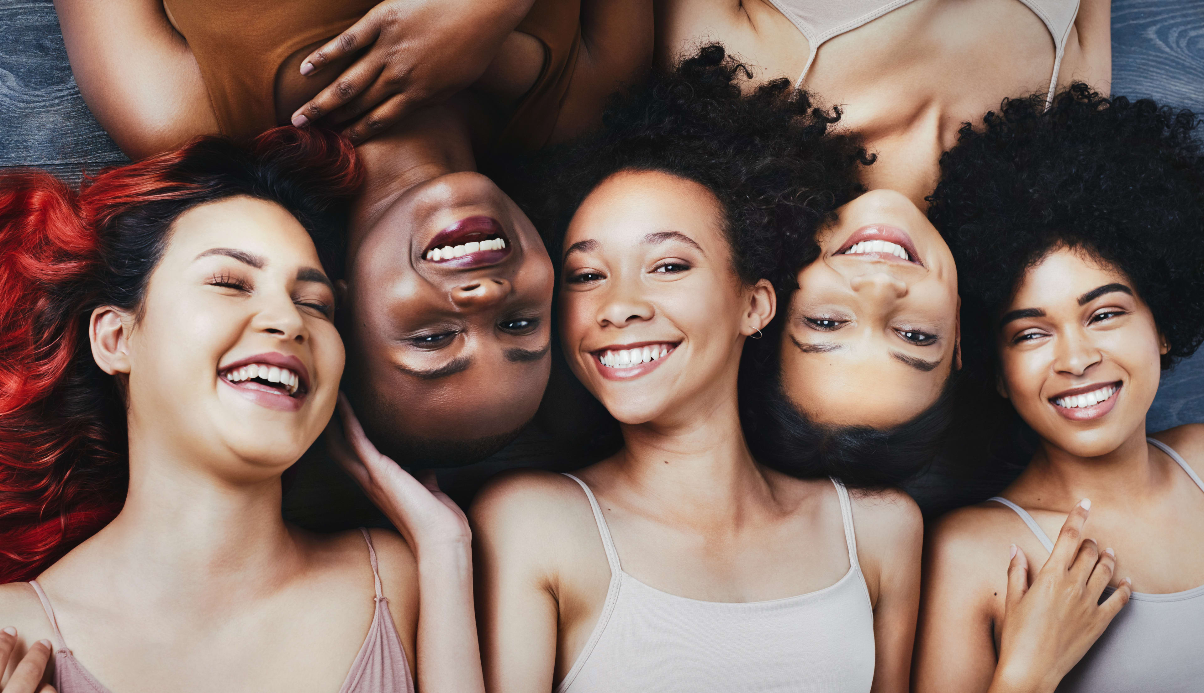 a group of young women with different colored skin tones smiling