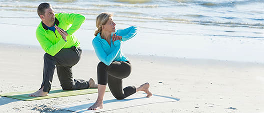 man and woman doing yoga on the beach