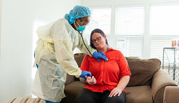 Home health nurse examines patient in her home