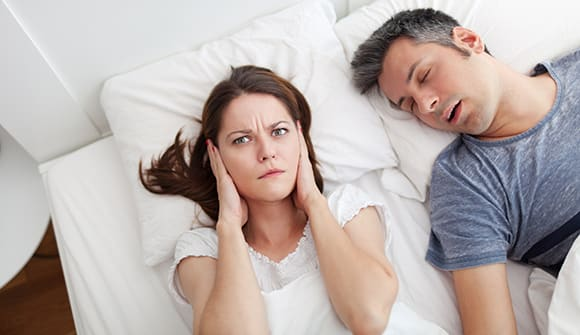 woman with hands over her ears with husband sleeping