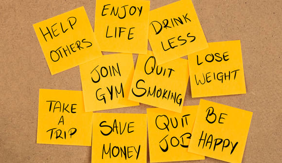 "Sticky notes with resolutions: ""Lose weight,"" ""Help others,"" ""Quit Smoking."""