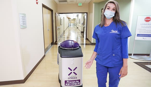 Nurse standing next to cleaning robot