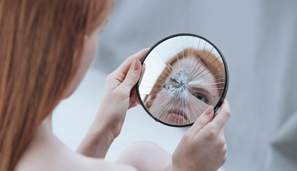 Woman looking into a shattered mirror