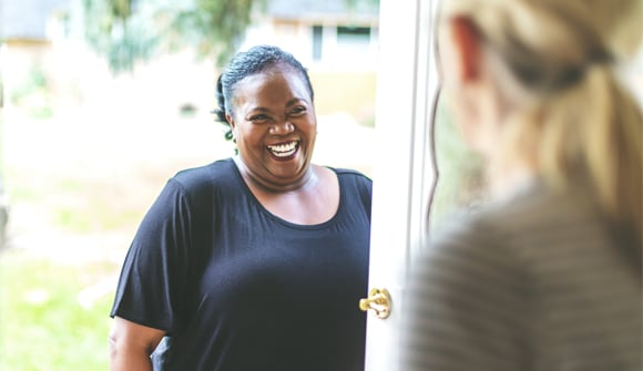 Woman is greeted at a friend's front door