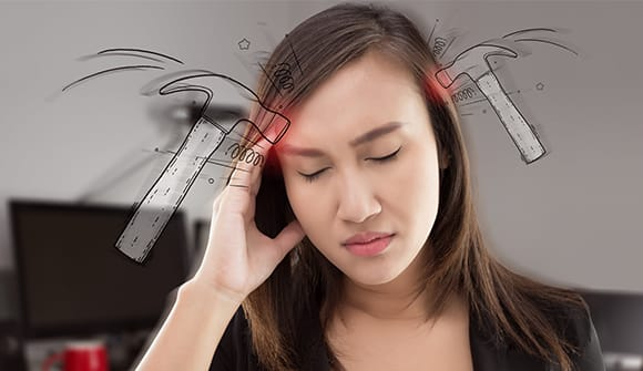 Woman with hand up to her head in pain
