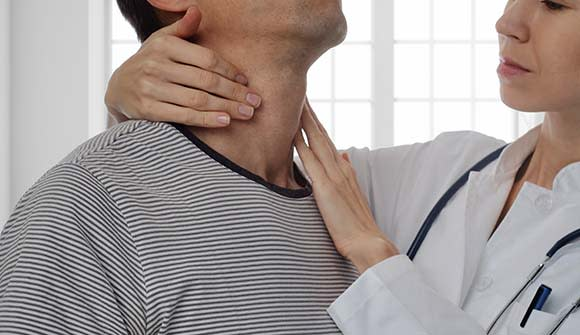 Female physician checking for a lump in man's neck