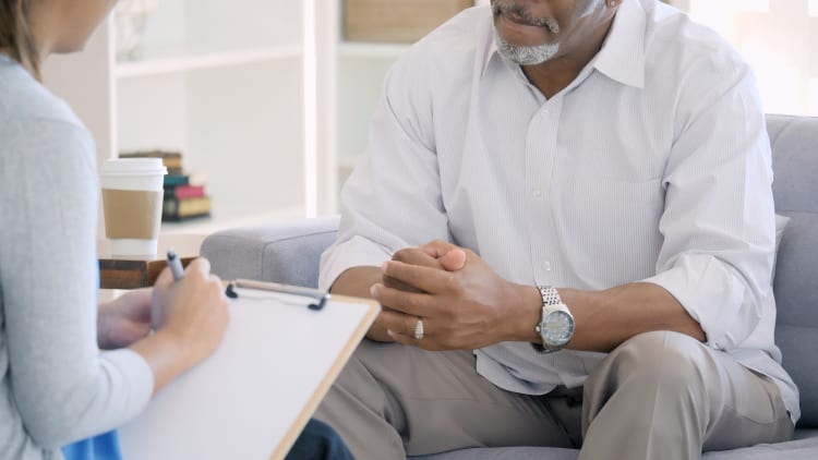 man sitting in a soft chair with his hands folded being interviewed by a female behavioral health therapist for sleep issues.