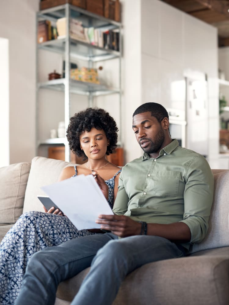 An african-american couple in their 30s sitting on a sofa of their home reading an advance directive document.