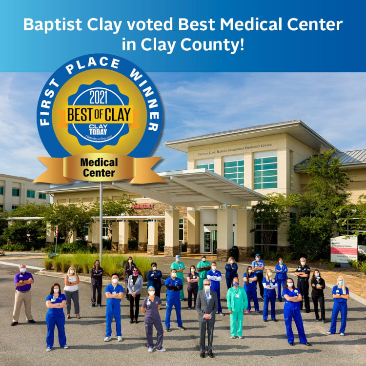 """A group of Baptist Health employees standing in front of the Baptist Clay building with text overlay that says """"Baptist Clay voted Best Medical Center in Clay County!"""""""