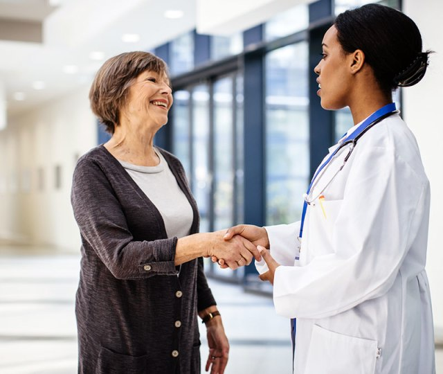 A female physician shakes hands with a female, senior patient wearing a cardigan.