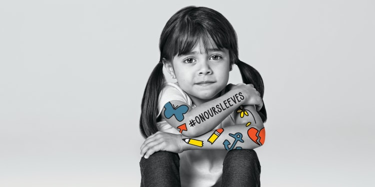 a school age child with dark hair sits, looking at the camera, and has colorful artwork on her arms, and the hashtag On Our Sleeves.