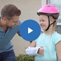 Little girl with arm cast and helmet smiling at her dad