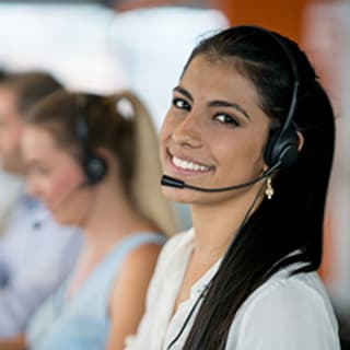 woman with dark long hair wearing a telephone operator headset smiling at you