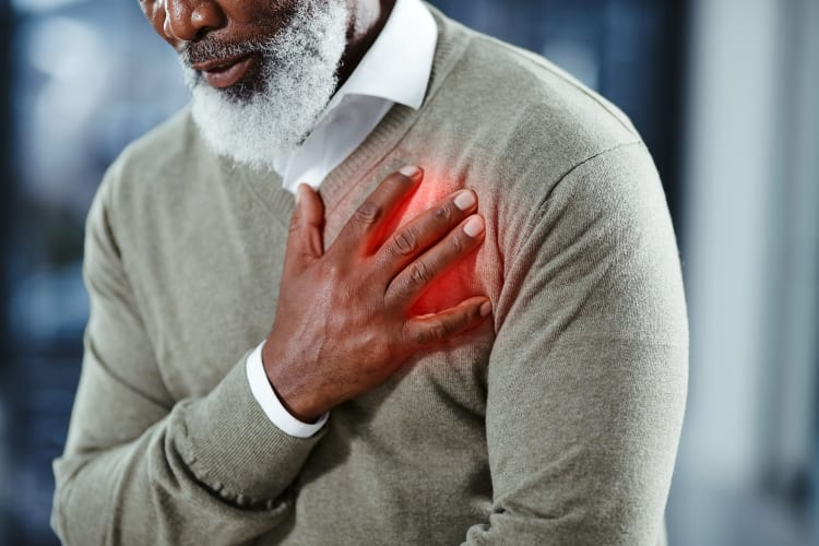 man with his hand on his chest where his heart is