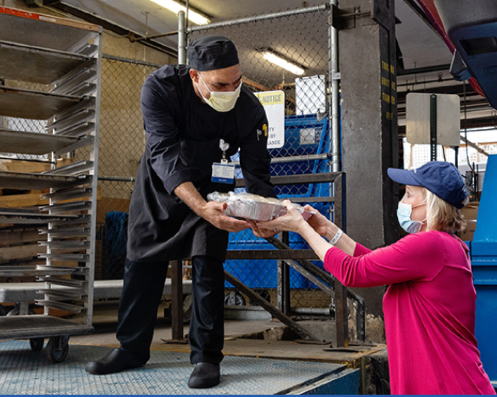 food service worker wearing face mask handing packaged food to a woman in a face mask