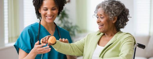 Nurse helping elderly woman with rehab