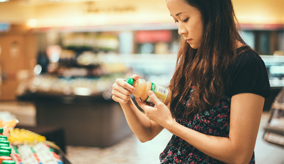 Asian woman studying food item in grocery store