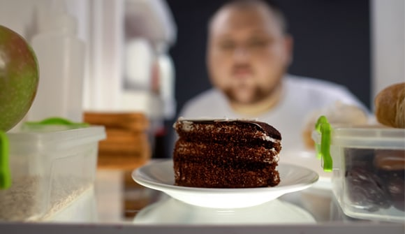 Man looking at chocolate cake in refrigerator