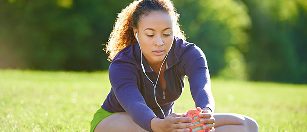 woman with headphones outside stretching her right leg