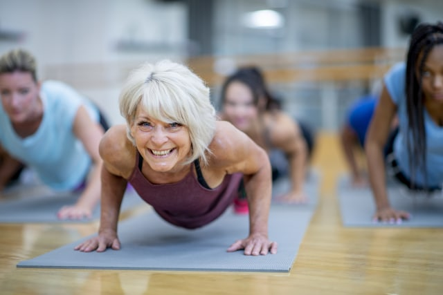 a woman smiling participating in a yoga class
