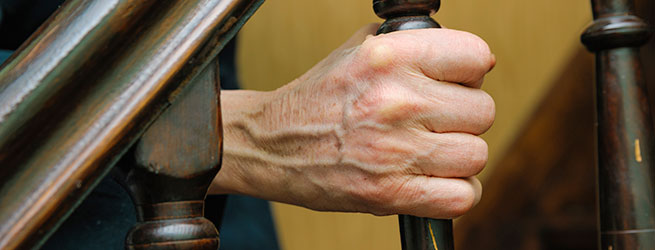 Hand grasping the banister of a staircase