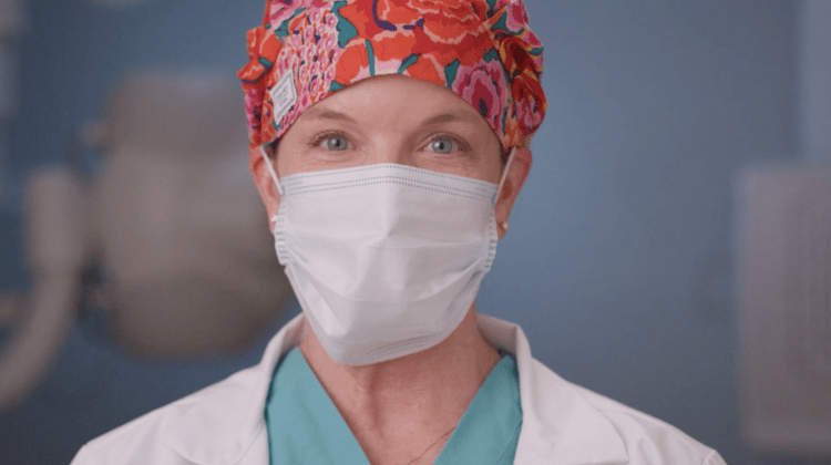 Upclose image of Female Health care Provider's face wearing a surgical mask.