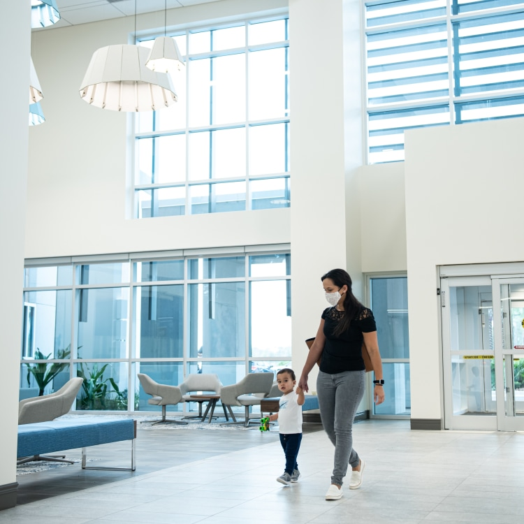 mother and toddler son walking hand in hand in the ligh-filled lobby of HealthPlace at Nocatee