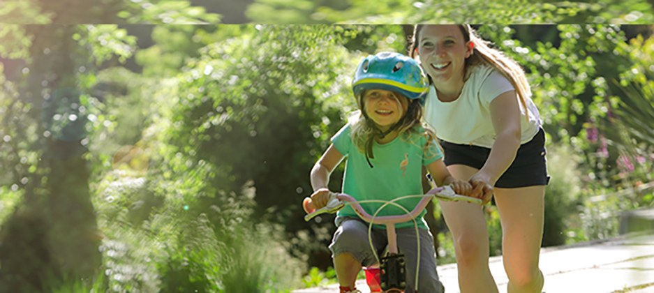 mom teaching her daughter to ride a bike outdoors