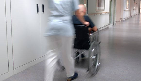 A nurse transports a patient in a wheelchair.
