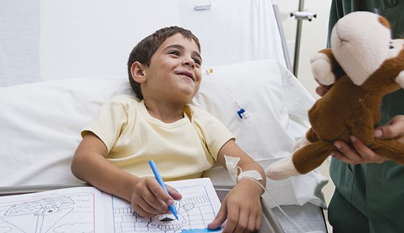 boy coloring in hospital bed
