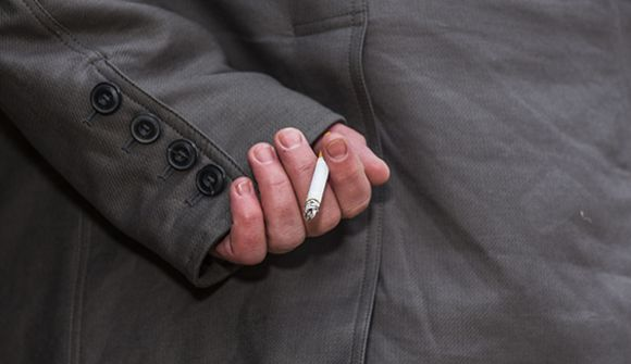 Man with cigarette hidden behind his back