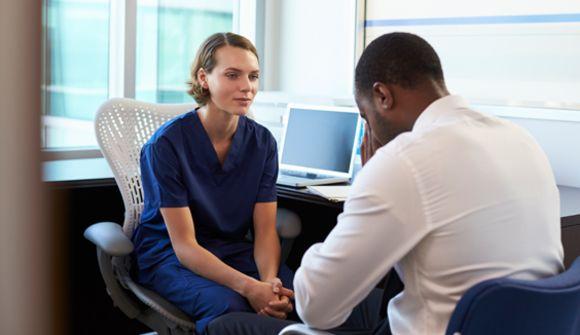 A nurse converses with a patient.