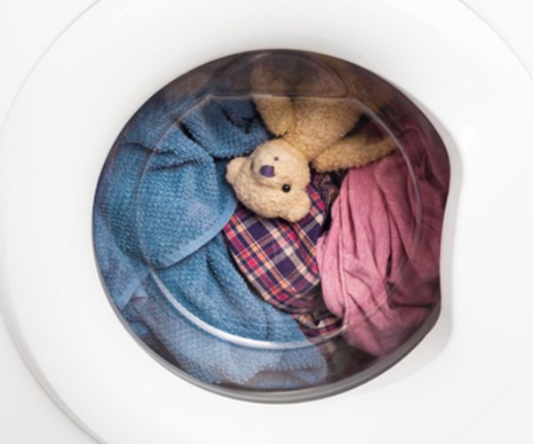 A teddy bear, towel and clothing spin in the dryer.