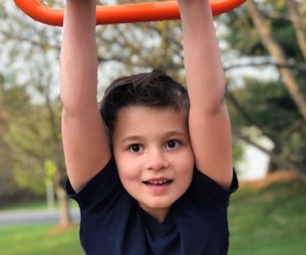 young boy swinging on monkey bars