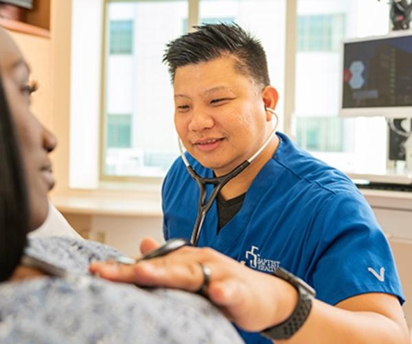 Baptist Health nurse listening to a female patient's heart