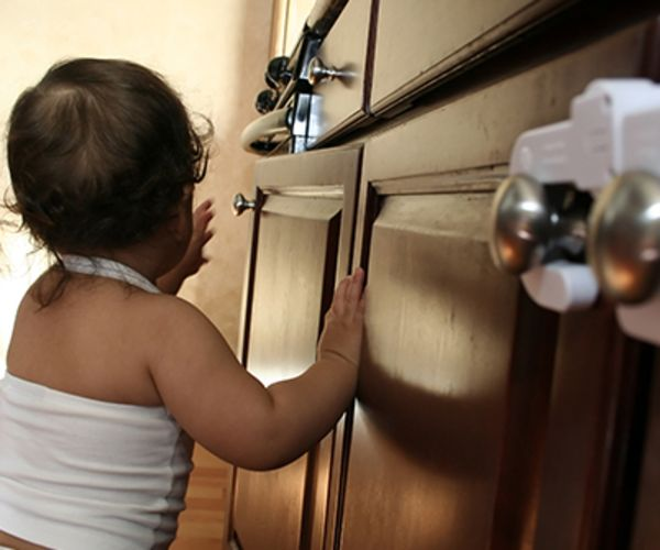 A baby investigates cabinets with baby locks.
