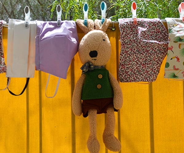 Cloth face masks and a stuffed animal hanging on a clothes line.