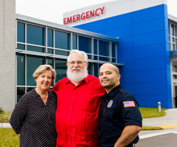 Patient Jim Markert standing next to his wife Timmi and Luis Vargas, the security guard who administered CPR and helped save his life.