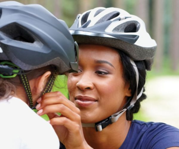 mom fastening helmet on child
